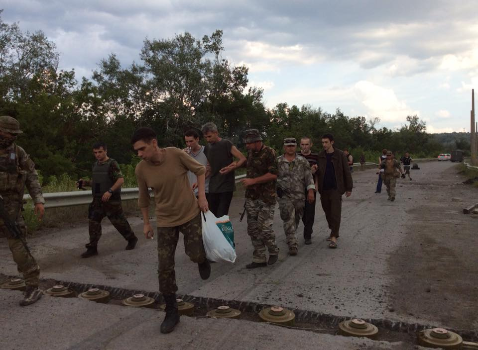 Ukrainian hostages crossing bridge near Shchastya