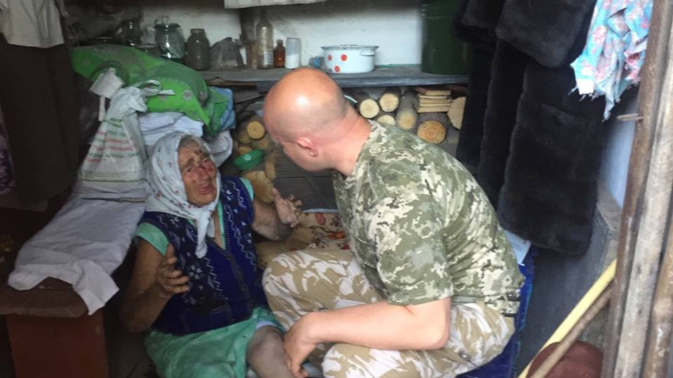 Mykhaylo Pukhtayevych helps wounded old lady in Toshkivka